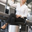 Stock Photo: Businesswomin office space throwing garbage in bin