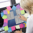 Businesswoman in office pointing at monitor with notes on it — Stock Photo #4766879