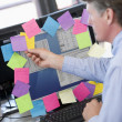 Businessman in office at monitor with notes on it — Stock Photo #4766881