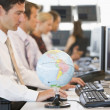 Five businesspeople in office space with a desk globe in foregro - Foto Stock