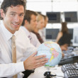 Businessman in office space with a desk globe — Stock Photo