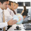Businessman in office space with a desk globe — Stock Photo #4766894