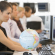 Stock Photo: Five businesspeople in office space with desk globe in foregroun