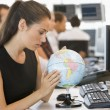 Businesswoman in office space with desk globe — Stock Photo