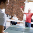 Stock Photo: Two men in office space playing ping pong