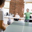 Two men in office space playing ping pong - Stock Photo