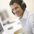 Man wearing headphones in computer room typing and smiling — Stock Photo