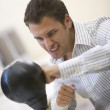 Man sitting in computer room using small punching bag for stress — Stock Photo #4766982