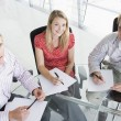 Three businesspeople in a boardroom with paperwork smiling — Stock Photo #4767064