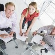 Three businesspeople in a boardroom with paperwork smiling — Stock Photo