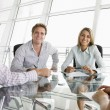 Four businesspeople in a boardroom with paperwork smiling — Stock Photo #4767068