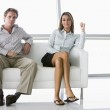 Two businesspeople sitting in office lobby smiling — Stock Photo