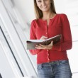Woman standing in corridor with personal organizer smiling — Stock Photo #4767088