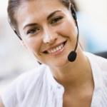mujer que llevaba auriculares sonriendo en el interior — Foto de Stock