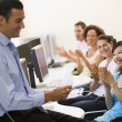 Man with clipboard giving lecture in applauding computer class - Stock Photo