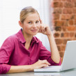 Businesswoman sitting in office with laptop smiling - Stockfoto