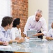 Stock Photo: Five businesspeople in boardroom with laptop