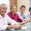 Foto Stock: Four businesspeople in boardroom smiling