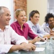 Four businesspeople in boardroom smiling — Stock Photo #4767224