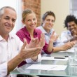 Four businesspeople in boardroom applauding and smiling - Foto Stock