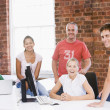 Five businesspeople in office space smiling — Stock Photo