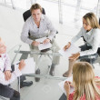 Four businesspeople in boardroom with paperwork — Stock Photo #4767283