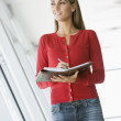 Woman standing in corridor writing in personal organizer — Stock Photo #4767289