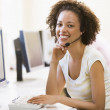Woman wearing headset in computer room smiling — Stock Photo