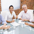 Four businesspeople in boardroom smiling — Stock Photo #4767335