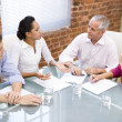 Foto Stock: Four businesspeople in boardroom meeting