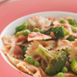 Pasta Bows with Tomato Sauce Broccoli and Peas - Stock Photo