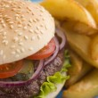 Beefburger with Salad and Pickles in a Sesame Seed Bun with Chip - Stock Photo