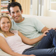 Couple in living room reading newspaper and smiling — Stock Photo