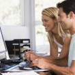 Couple in home office using computer and smiling - Lizenzfreies Foto