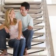 Couple sitting on staircase smiling — Stock Photo