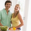 Couple in kitchen cutting up vegetables and smiling — Stock Photo