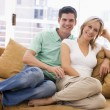 Couple in living room smiling - Foto Stock