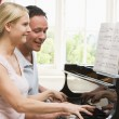Couple playing piano and smiling — Stock Photo