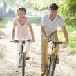 Couple on bikes outdoors smiling — Stock Photo #4767757