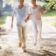 Couple running outdoors holding hands and smiling — Stock Photo #4767763