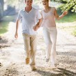 Couple running outdoors holding hands and smiling — Stock fotografie