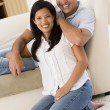 Couple in living room smiling — Stock fotografie #4767777