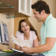 Couple in kitchen with computer and newspaper smiling - Photo