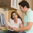 Couple in kitchen with computer and newspaper smiling — Stock Photo