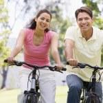 Couple on bikes outdoors smiling — Stock Photo #4767784