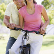 Couple on a bike outdoors smiling - Stock Photo
