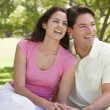 Couple sitting outdoors smiling — Stock Photo