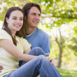 Couple sitting outdoors smiling — Stock Photo #4767799