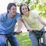 Couple on bikes outdoors smiling — Stock Photo #4767803