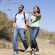 Couple walking on path holding hands and smiling — Stock Photo